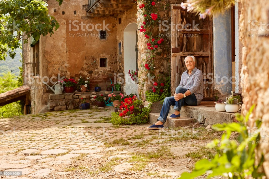 Portrait of smiling senior man sitting on porch