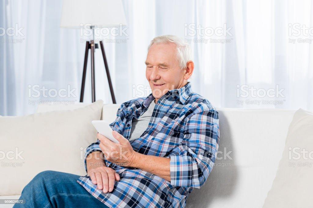 Retrato de sonriente hombre mayor sentado en el sofá y con smartphone en casa - Foto de stock de Adulto libre de derechos