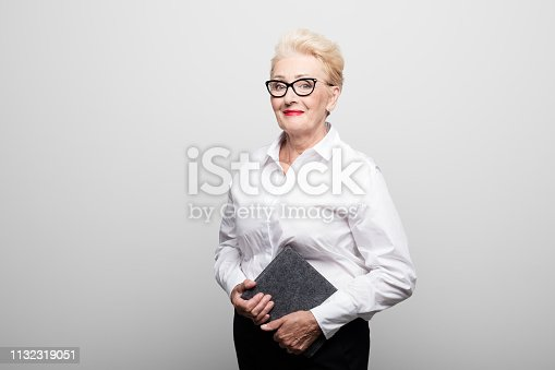 Portrait of smiling senior manager holding diary. Confident female professional is standing against white background. She is wearing formals.
