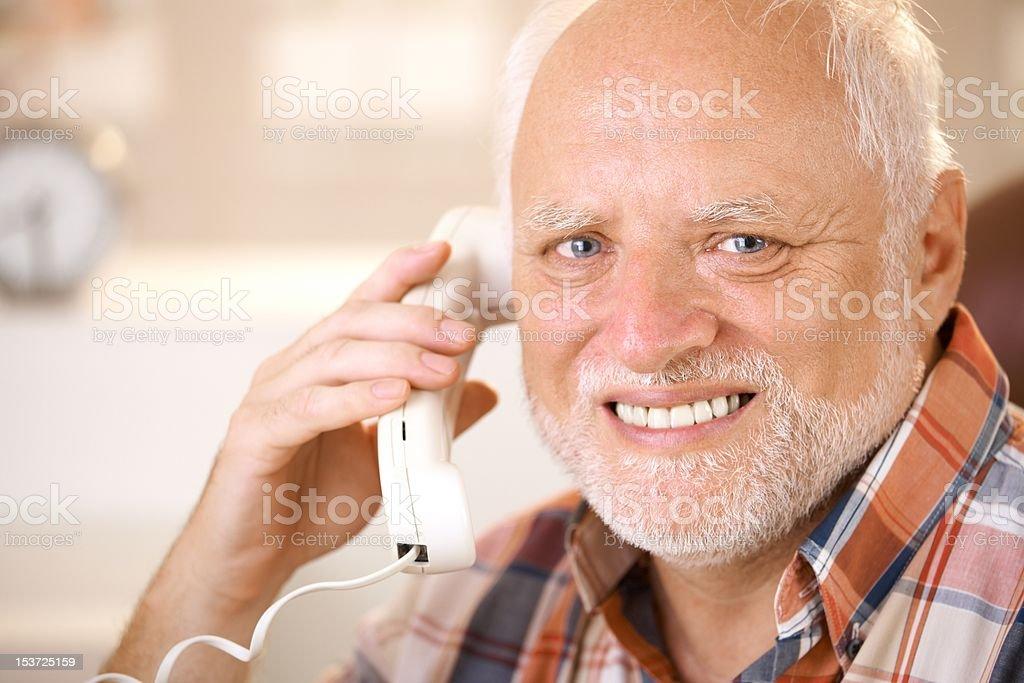 Portrait of smiling senior using landline phone Closeup portrait of smiling senior man using landline phone, looking at camera... 60-69 Years Stock Photo