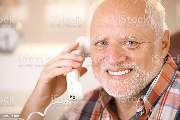 Portrait Of Smiling Senior Using Landline Phone Stock Photo - Download Image Now