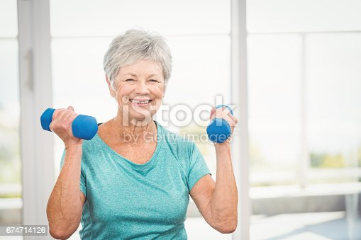 istock Portrait of smiling senior woman holding dumbbell 674714126