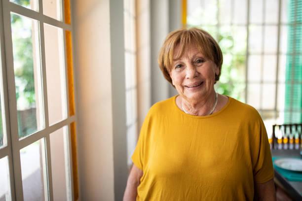 Porträt einer lächelnden Seniorin in der Nähe des Fensters – Foto