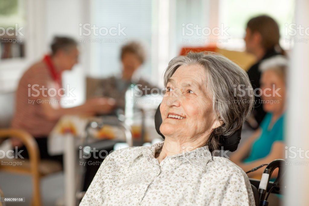 Portrait Of Smiling Senior Woman On Wheelchair stock photo