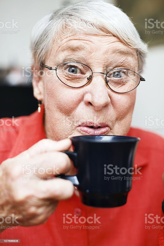 Portrait of smiling senior woman sipping coffee royalty-free stock photo