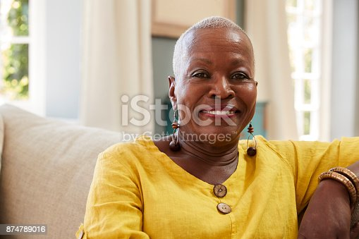 istock Portrait Of Smiling Senior Woman Sitting On Sofa At Home 874789016
