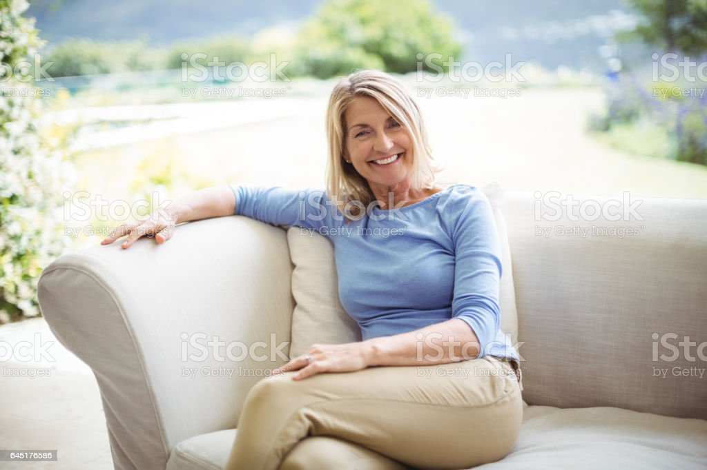 Portrait of smiling senior woman sitting on sofa in living room stock photo