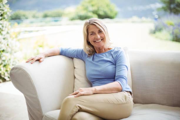 portret van lachende senior vrouw zittend op de bank in de woonkamer - vrouw 60 stockfoto's en -beelden