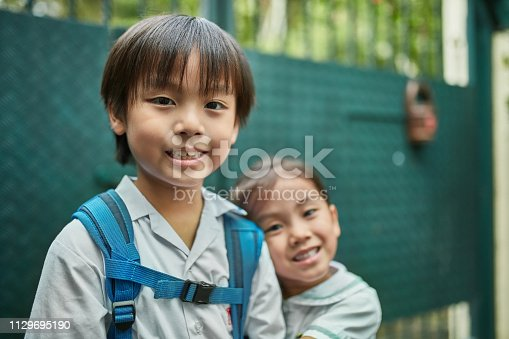 Portrait of cute loving siblings standing against gate. Happy brother and sister are going to school. They are in uniforms.