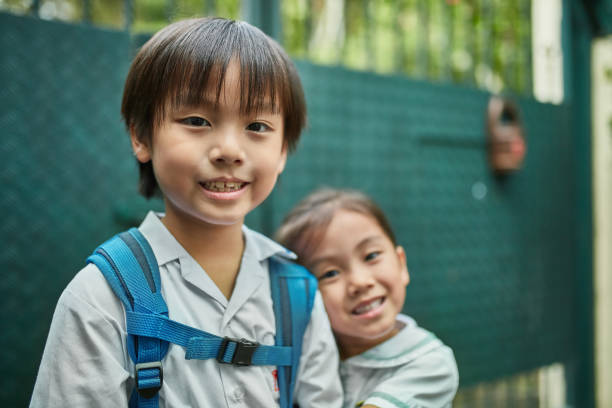 Portrait of smiling siblings going to school stock photo