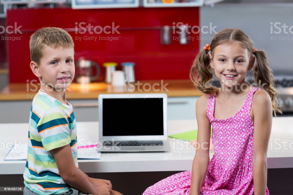 Portrait of smiling siblings with laptop in kitchen royalty-free stock photo