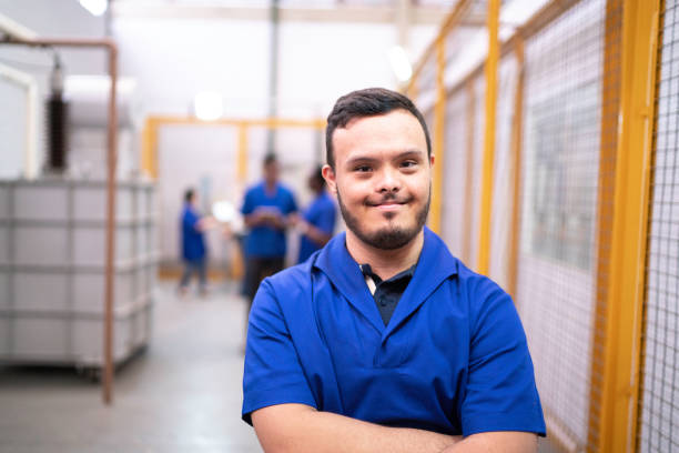 Portrait of smiling special needs employee in industry Portrait of smiling special needs employee in industry persons with disabilities stock pictures, royalty-free photos & images