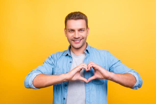 黄色の背景の上の指で無精ひげを示す心図と男は見事な笑みを浮かべての肖像画 ストックフォト