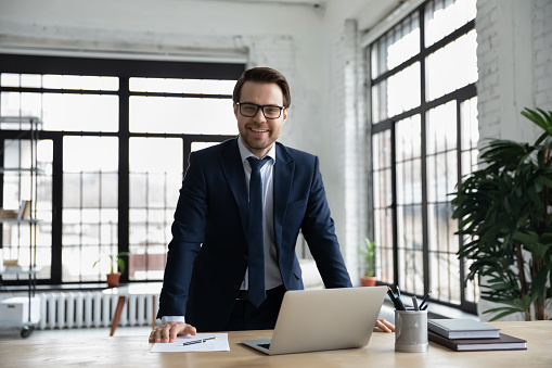 825082848 istock photo Portrait of smiling successful businessman posing at workplace 1248296815