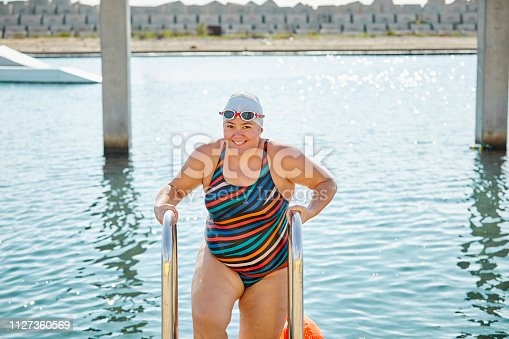 Portrait of smiling female swimmer coming out of sea. Mature woman is enjoying summer vacation. She is in swimwear on sunny day.