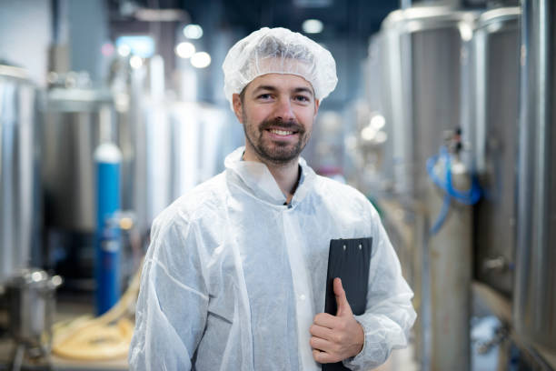 Portrait of smiling technologist in industrial plant. Portrait of smiling technologist in industrial plant. hair net stock pictures, royalty-free photos & images