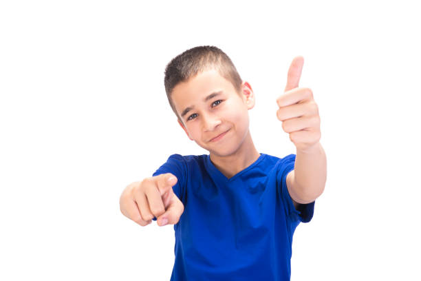 Portrait of smiling teenage boy gesturing thumbs up while he pointing at camera over white background