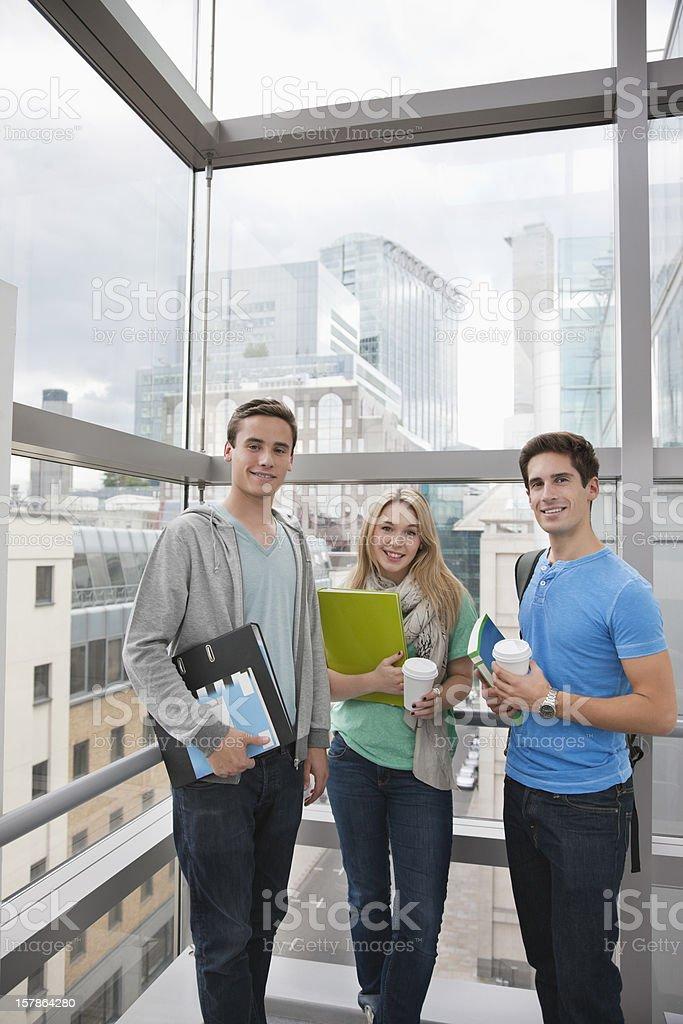 Portrait of smiling university students near window royalty-free stock photo