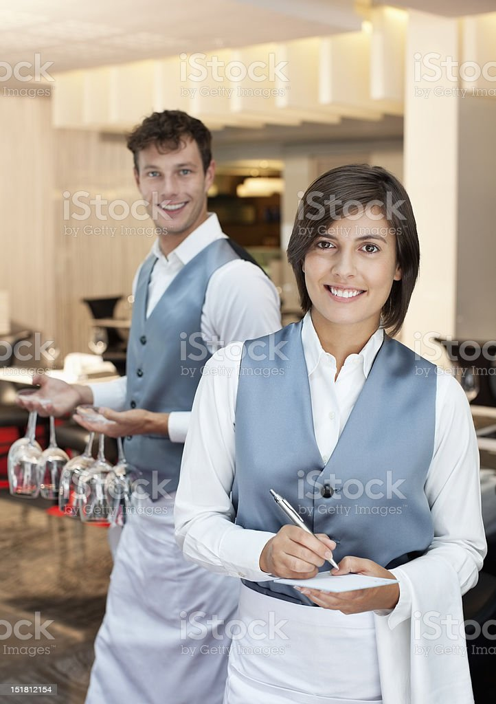 Portrait of smiling waiter and waitress in restaurant stock photo