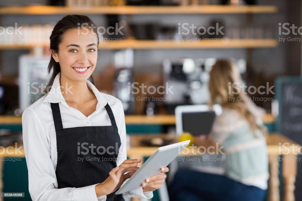 Portrait of smiling waitress using digital tablet stock photo
