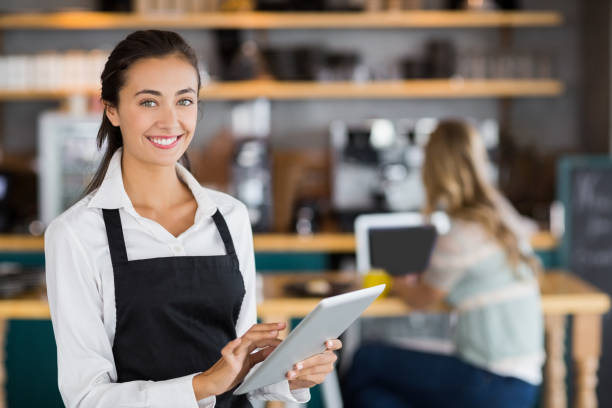 Portrait of smiling waitress using digital tablet Portrait of smiling waitress using digital tablet in cafe waiter stock pictures, royalty-free photos & images