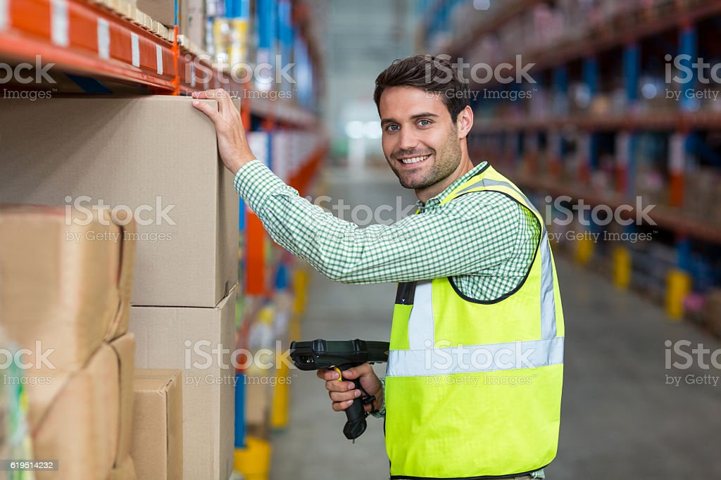 Portrait of smiling warehouse worker scanning box stock photo