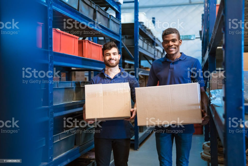 Portrait of smiling warehouse workers with boxes Portrait of smiling male warehouse workers carrying cardboard boxes. Colleagues are standing in distribution workshop. They are working together. 20-24 Years Stock Photo