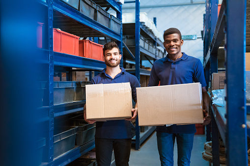Portrait Of Smiling Warehouse Workers With Boxes Stock Photo - Download Image Now