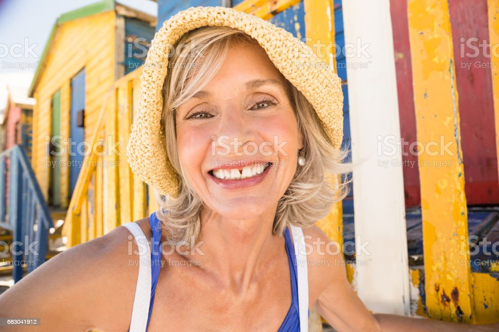 Portrait of smiling woman against beach huts royalty-free stock photo
