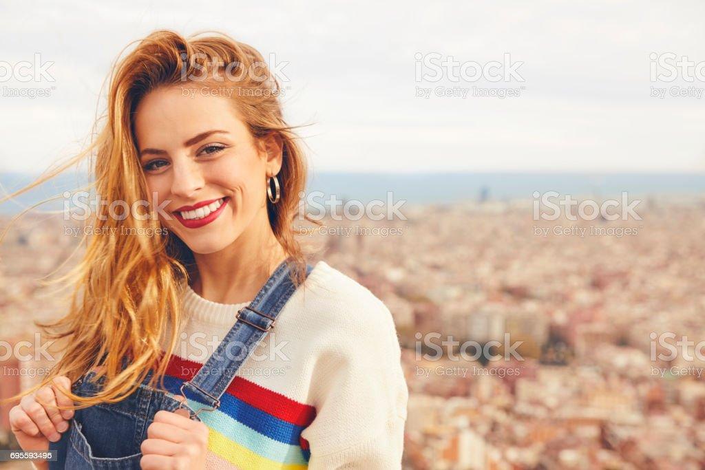 e0bf2561c Retrato de uma mulher sorridente contra a paisagem urbana foto royalty-free