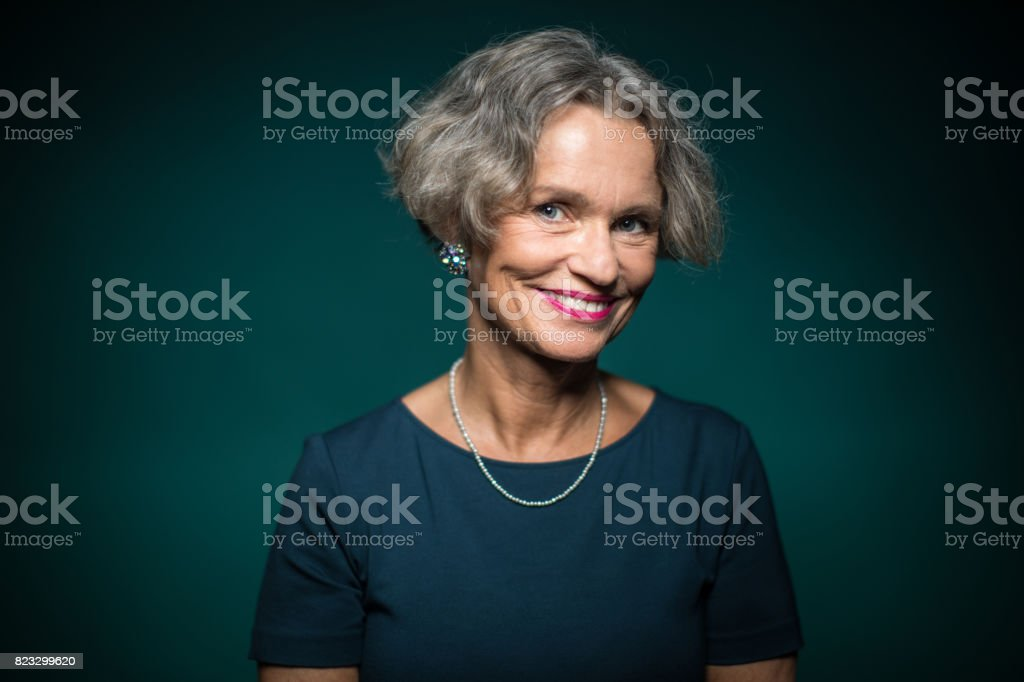 Portrait Of Smiling Woman Against Green Background stock photo
