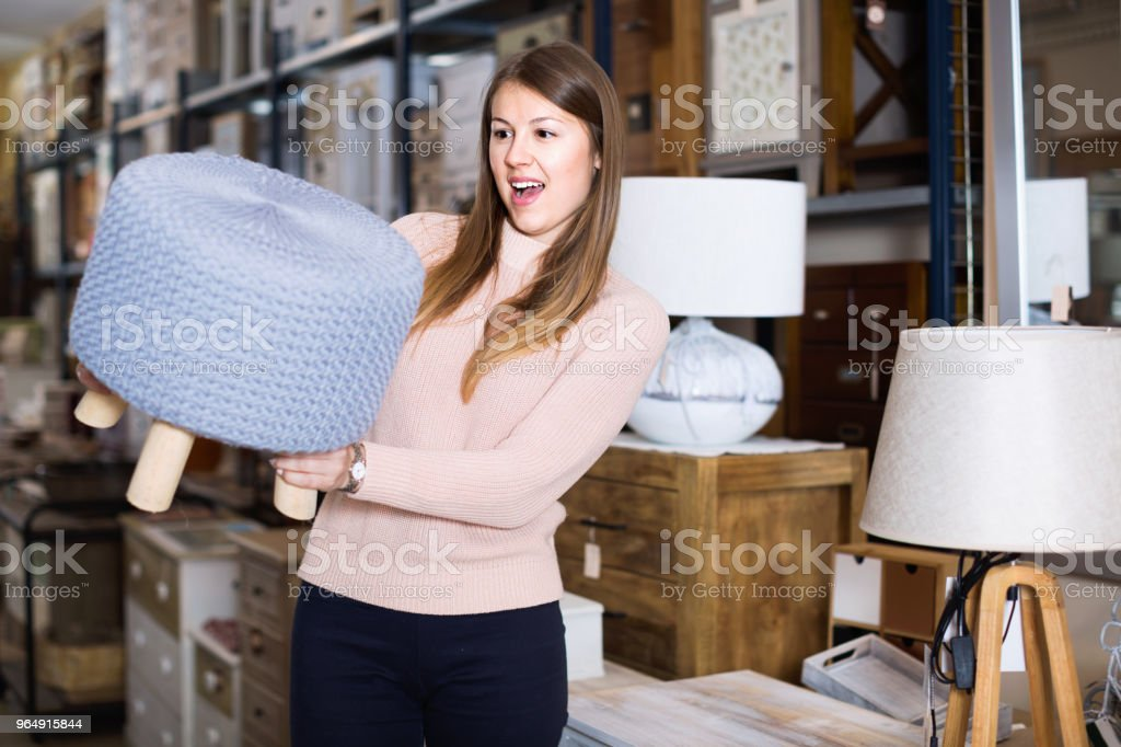 portrait of smiling woman buyer choosing pouf in furniture shop royalty-free stock photo