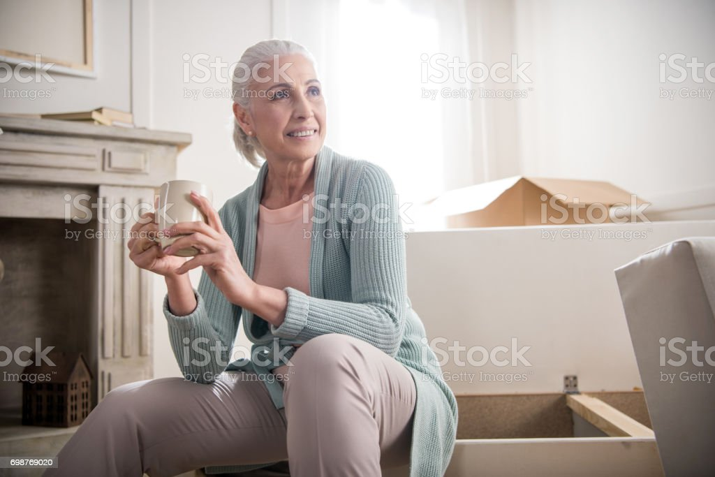 portrait of smiling woman drinking coffee and looking away at home stock photo