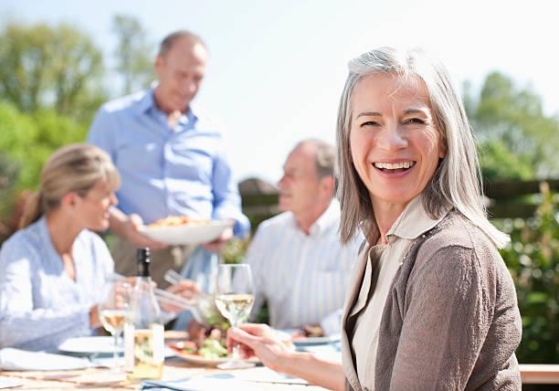 retrato de mujer sonriente bebiendo vino en mesa en el patio - couple lunch outdoors fotografías e imágenes de stock