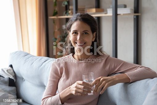 Portrait of smiling young Caucasian woman sit on couch hold glass of clean mineral water follow healthy lifestyle, happy millennial female enjoy aqua for body hydration, wellness, healthcare concept