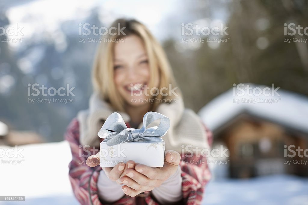 Portrait of smiling woman holding Christmas gift in front of cabin stock photo