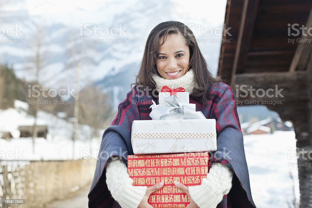 Portrait of smiling woman holding Christmas gifts royalty-free stock photo