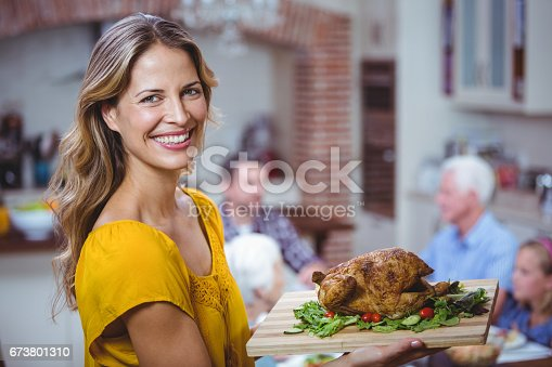 Portrait of smiling woman holding cutting board with meat at home