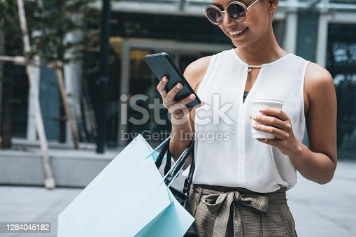 Close up portrait of beautiful smiling short hair blonde woman standing in front of shopping mall. She is typing message on smartphone and holding shopping bag and coffee