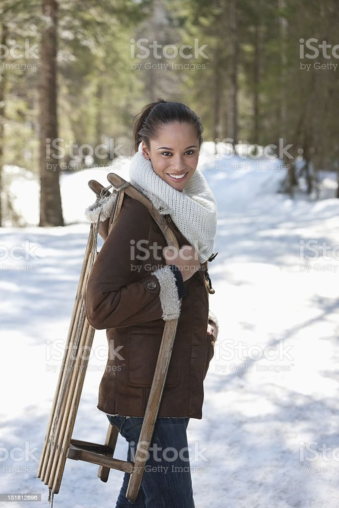Portrait of smiling woman holding sled in snowy woods royalty-free stock photo