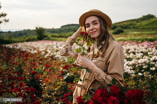 Portrait of beautiful woman looking at camera and smiling in a rose field.