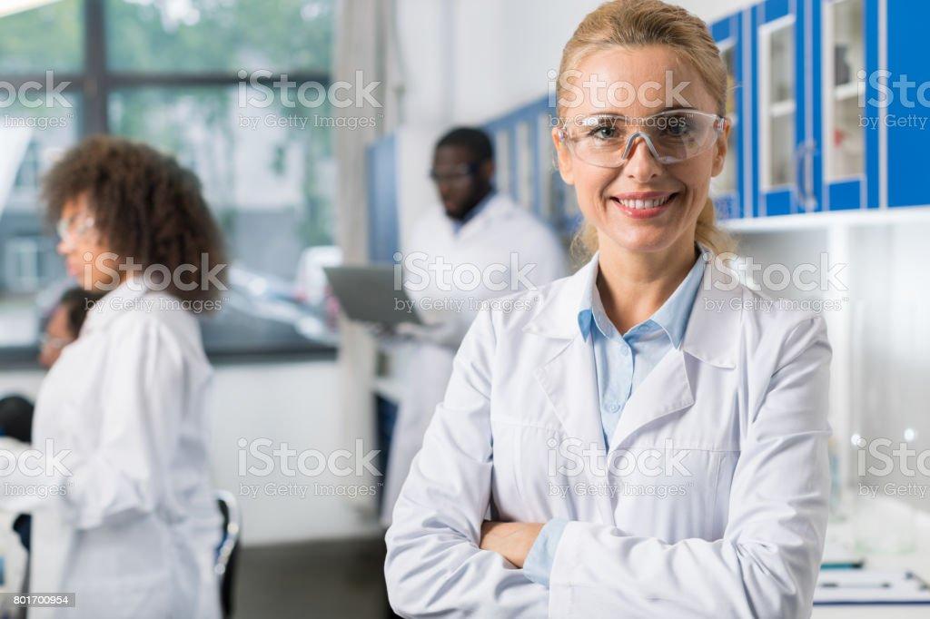 Porträt von lächelnden Frau im weißen Kittel und schützende Brillen In modernen Labor, Wissenschaftlerin über beschäftigt Forscher-Team – Foto