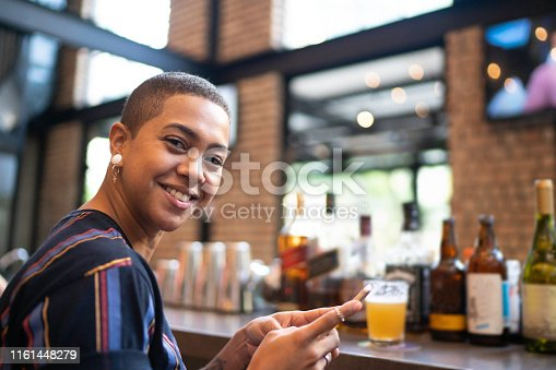 istock Portrait of smiling woman looking at camera while using phone 1161448279