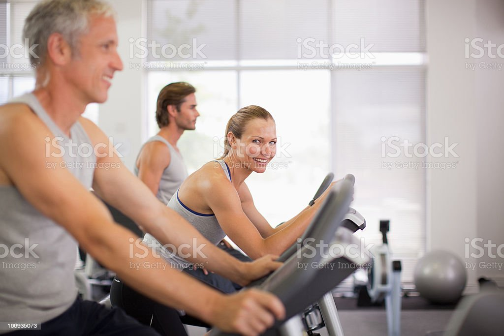 Portrait of smiling woman on exercise bike in gymnasium royalty-free stock photo