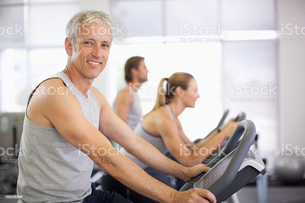 Retrato de mujer sonriente en máquinas de ejercicios en el gimnasio - foto de stock