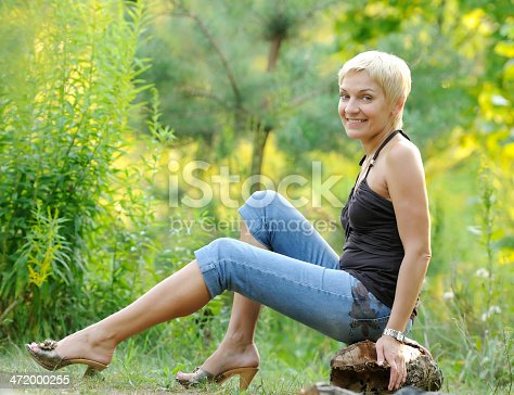 977601820 istock photo portrait of smiling woman outdoors 472000255