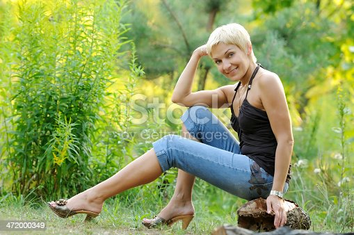 977601820 istock photo portrait of smiling woman outdoors 472000349