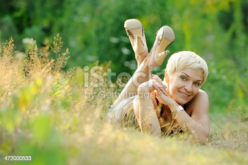 977601820 istock photo portrait of smiling woman outdoors 472000533