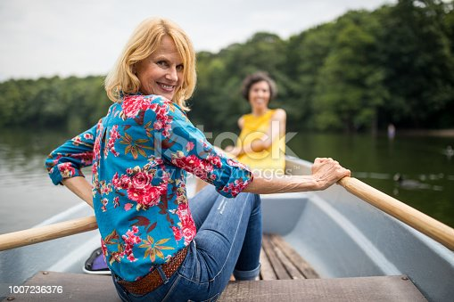 istock Portrait of smiling woman rowing boat in lake 1007236376