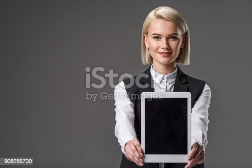 istock portrait of smiling woman showing tablet with blank screen 908286700